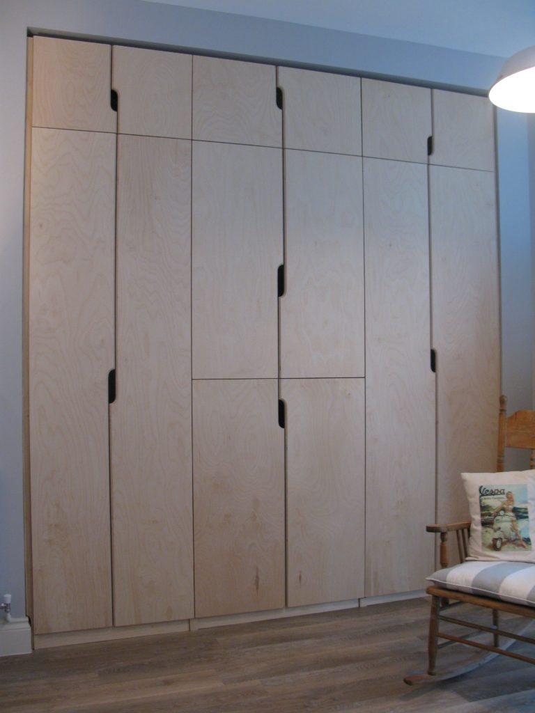 a big bank of ply wardrobes with top-boxes...... the handles are a simple flourish