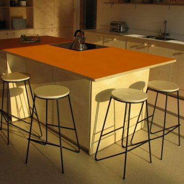 kitchen in natural birch ply with orange and white formica